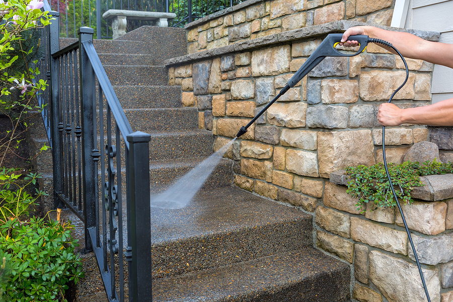 washing the house front entrance stair steps and stone walls with pressure power washer