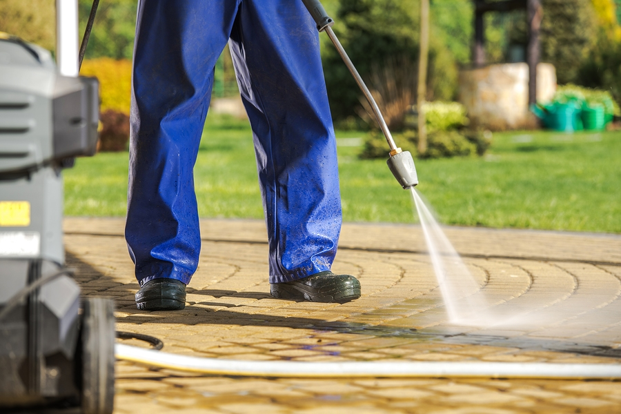 worker and pressure washer. men wearing rain coat cleaning brick paths using powerful water sprayer.