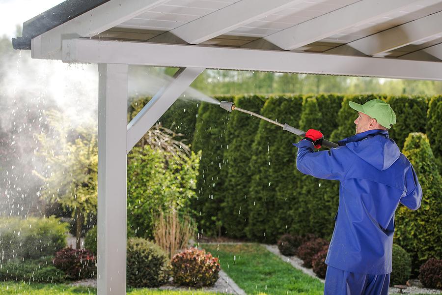 caucasian men in his 30s pressure washing garden porch wooden roof which get dirty during winter season. powerful garden wash.